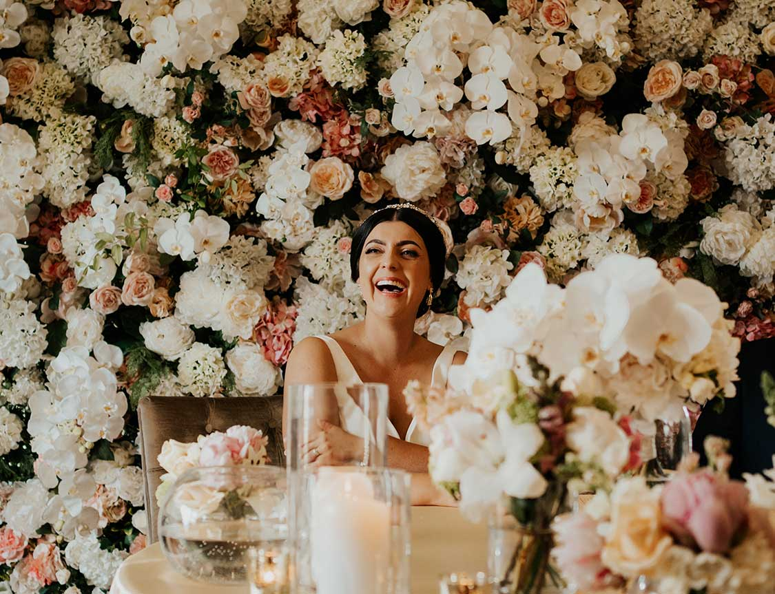 Laughing bride in front of flower wall