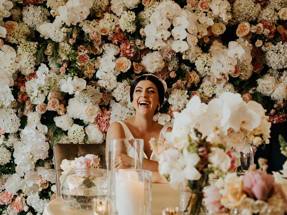 Beautiful bride in front of her wedding flower wall