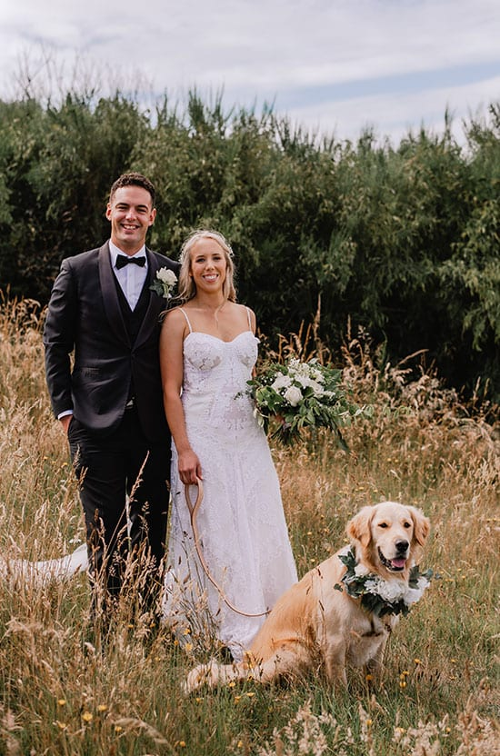 Bride and groom with their dog and bouquets